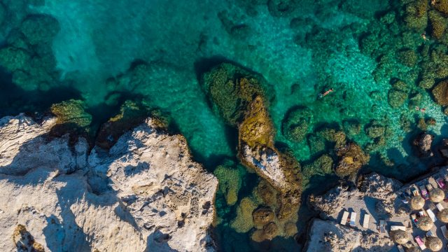 Turquoise Water and Rocky Shore on Greek Island, Aerial top Down View.